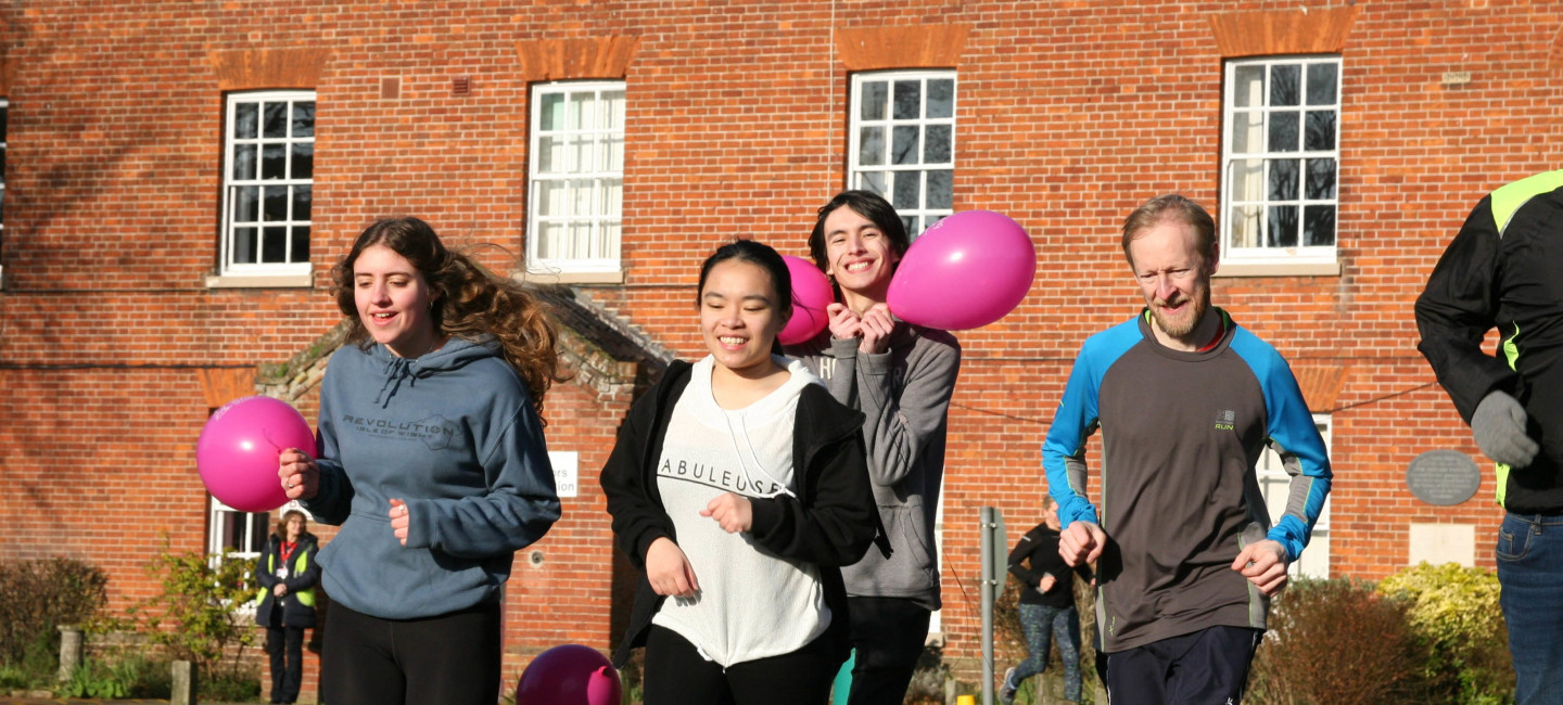 Students and staff running on Paston campus with pink balloons