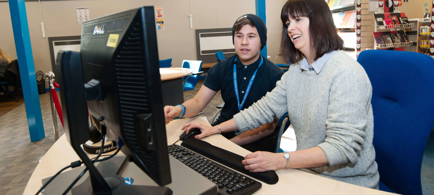Tutor supporting student at a computer in Paston college library