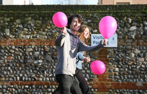 Students running through Paston car park with pink balloons