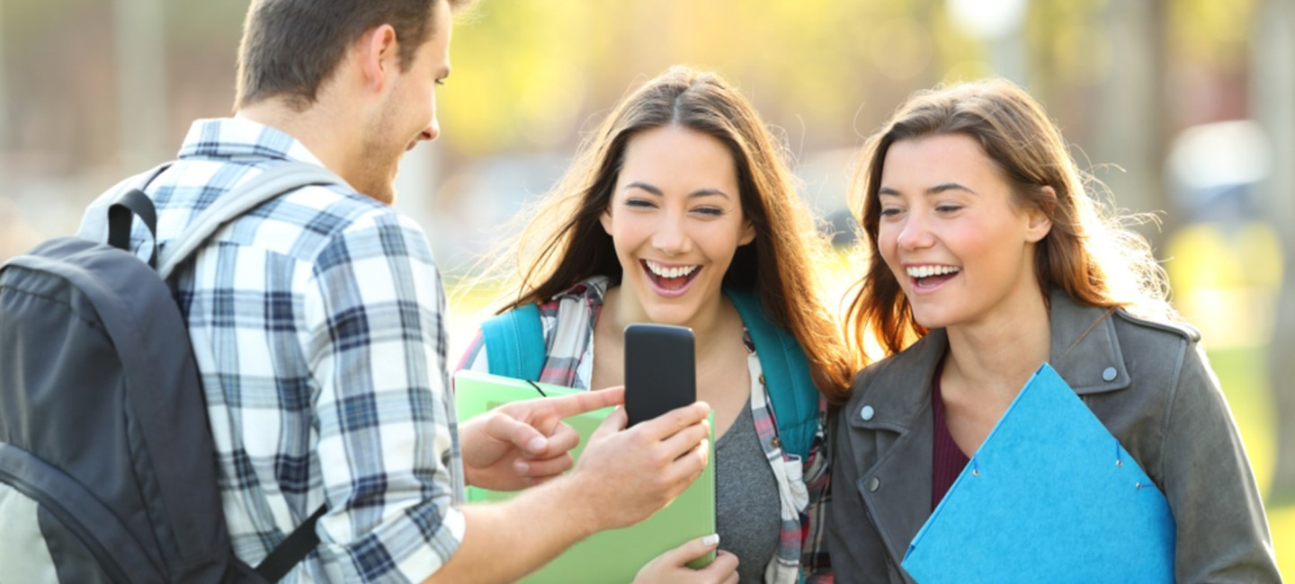 Two female students laughing at male student's mobile phone screen
