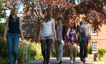 Students walking on pavement through Paston Lawns campus